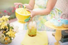 Lady pouring tea from a yellow and green ceramic tea kettle into a tall glass with ice