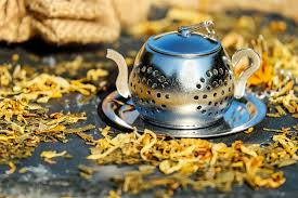 small silver tea pot on silver saucer surrounded by dried yellow tea leaves